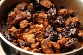 Добавьте к мясу чернослив без косточек. Тушите еще полчаса. Добавьте соль и специи.