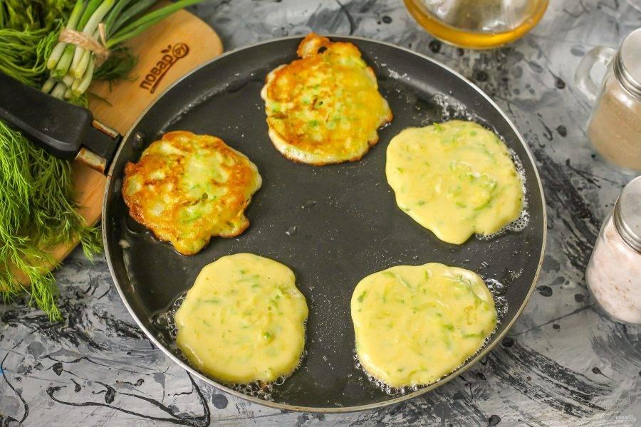 Раскалите сковороду с растительным маслом, нагрев уменьшите до умеренного и выложите в масло столовой ложкой порции теста. Обжарьте до румяности по минуте с каждой стороны. Выложите готовые оладьи на тарелку, обжарьте остальное тесто.