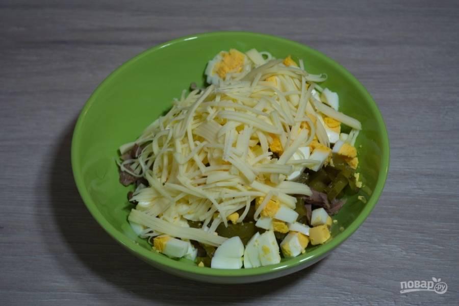 Все составляющие салата соедините в одной миске. Заправьте майонезом. Добавьте натертый на крупной терке сыр и снова перемешайте. Приправьте салат специями по вкусу.