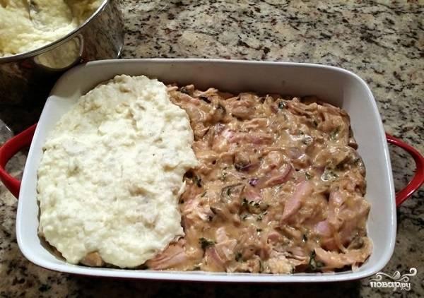 9. Дно жаропрочной формы смажьте немного маслом. Выложите на дно половину картофельного пюре. Распределите начинку и накройте оставшимся пюре. Присыпьте сверху сыром с сухарями, отправьте в разогретую до 180 градусов духовку.