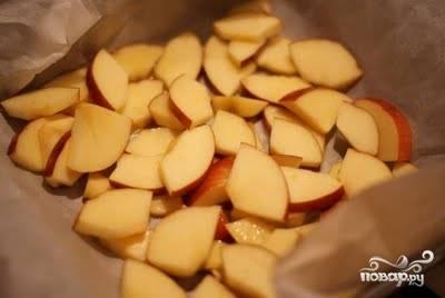 Форму для выпекания застилаем бумагой на нее выкладываем яблоки, нарезанные на достаточно крупные кубики (2 яблока).