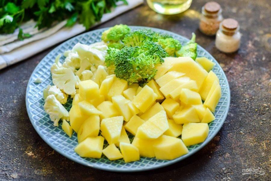 Очистите картофель, нарежьте крупно. Также сполосните и нарежьте цветную капусту, брокколи.