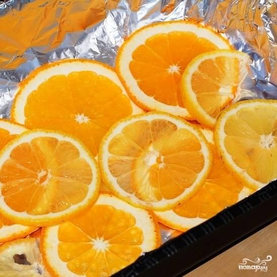 Противень застилаем фольгой. Оставшийся апельсин и половину лимона нарезаем тонкими дольками и выкладываем на противень.