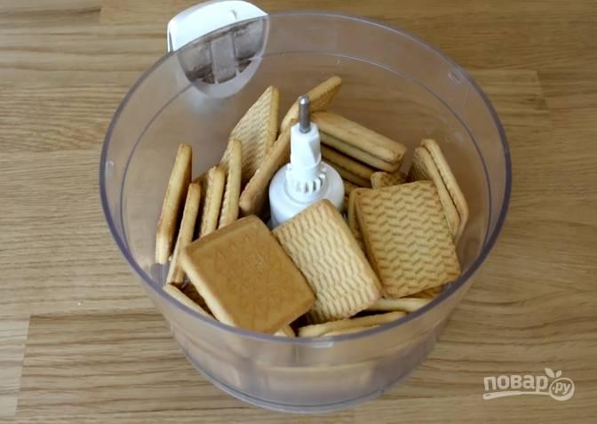 1. С помощью блендера или скалки измельчите песочное печенье в крошку.