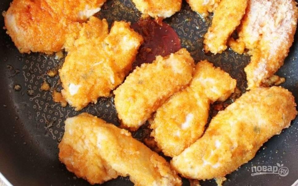 Разогрейте в сковороде растительное масло. Его должно быть достаточно, чтобы кусочки плавали в нем. Обжаривайте курицу в панировке со всех сторон до хрустящей корочки и золотистого цвета. Подавайте с зеленью и помидорами черри, дополнив остатками соуса.