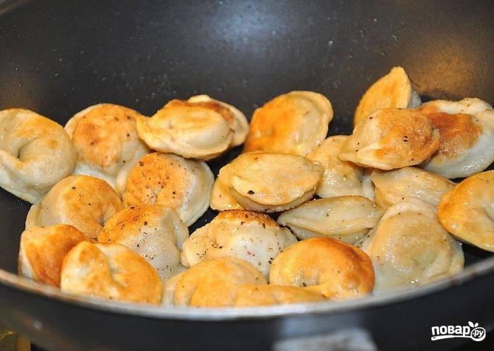2.Обжариваю пельмени до хрустящей и золотистой корочки, добавляю по вкусу соль и черный перец. Перекладываю пельмени в тарелку.