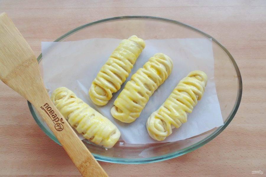 После смажьте пирожки яйцом и отправьте в духовку, разогретую до 175-180 градусов.