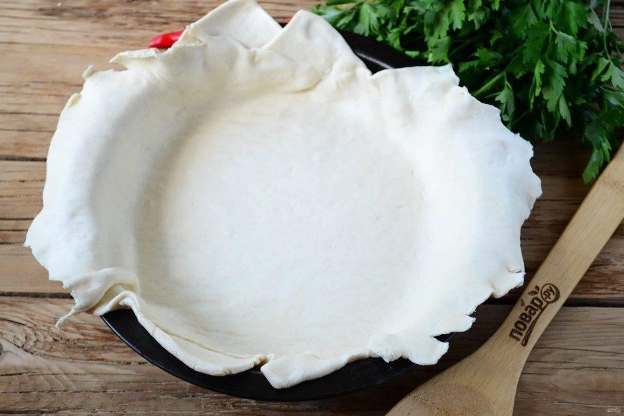 Тесто тонко раскатайте и положите в круглую форму для выпекания диаметром не более 23 см. Класть нужно так, чтобы образовались довольно большие бортики, которые будут свисать наружу.