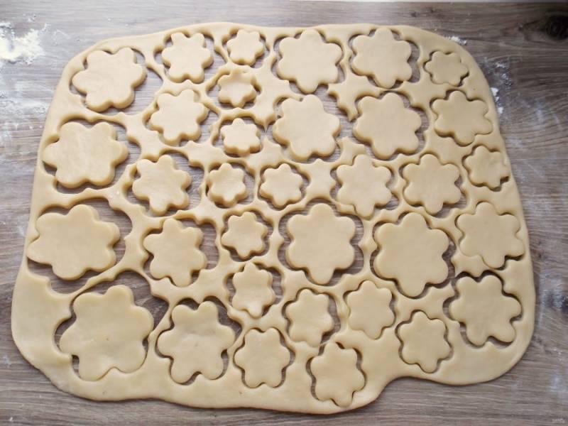 Присыпьте стол мукой, и раскатайте тесто толщиной не больше 1 сантиметра. Формочкой вырежьте фигурки или просто порежьте на ромбики.
