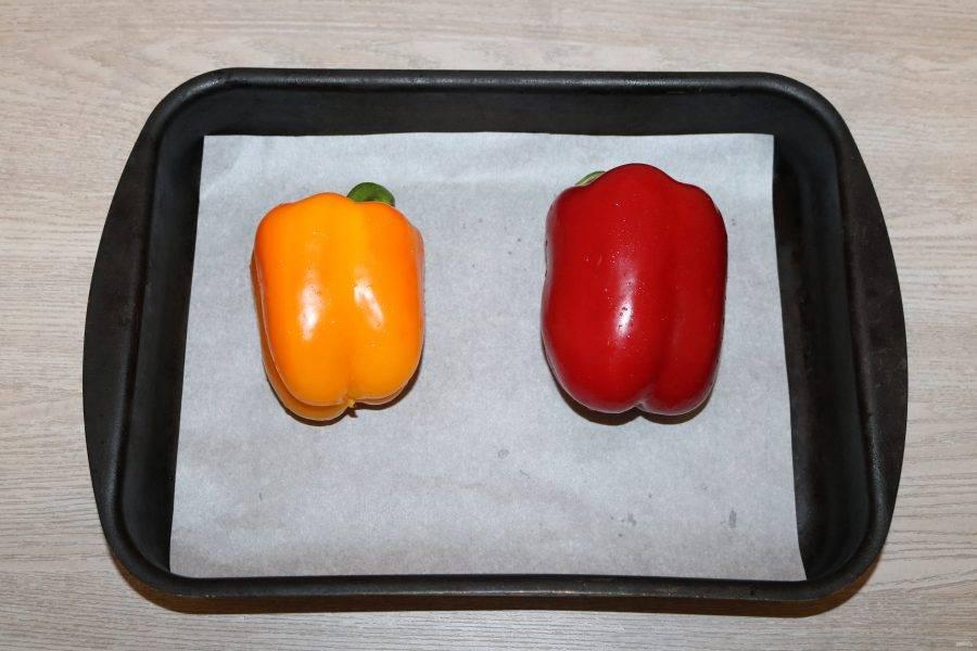 Сладкий перец выложите на противень, застеленный пергаментом. Отправьте в разогретую духовку до 200 градусов на 10 минут.