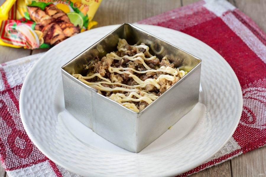 Выложите рыбу поверх картошки и полейте майонезом.