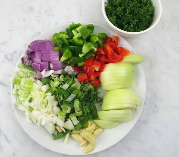 1. Первым делом необходимо подготовить овощи. Луковицу очистить и нарезать полукольцами. Сладкий перец, очистив от хвостиков и семян, небольшими кубиками. Чеснок можно разрезать пополам. Свежую зелень вымыть, просушить и также измельчить.