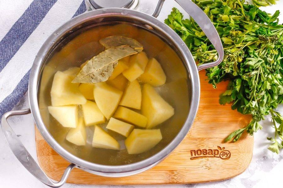 Очистите картофель от кожуры, промойте в воде и нарежьте средними кубиками. Высыпьте нарезку в кастрюлю и влейте горячую воду. Добавьте парочку лавровых листьев и отварите картофель примерно 8-10 минут.