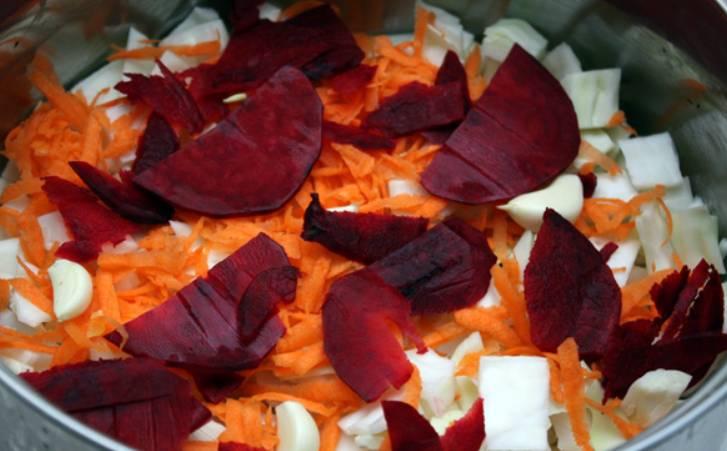 Теперь выкладываем все овощи слоями в большую кастрюлю. Также добавляем зубчики чеснока.