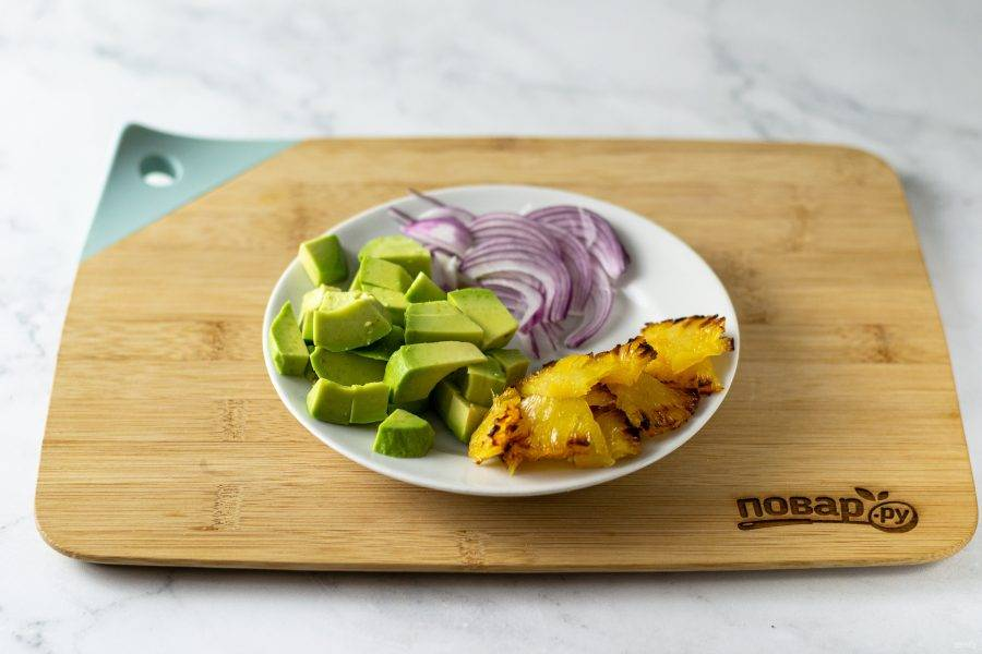 Остудите ананасы, нарежьте ломтиками. Нарежьте лук тонкими полукольцами, а авокадо кубиками.