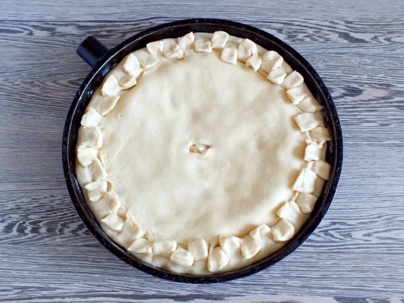 Соедините свободные края пластов. Тщательно скрепите. Оформите бортик на своё усмотрение. Накройте подготовленный пирог полотенцем и оставьте на 20 минут. За это время разогрейте духовку до 180 градусов.