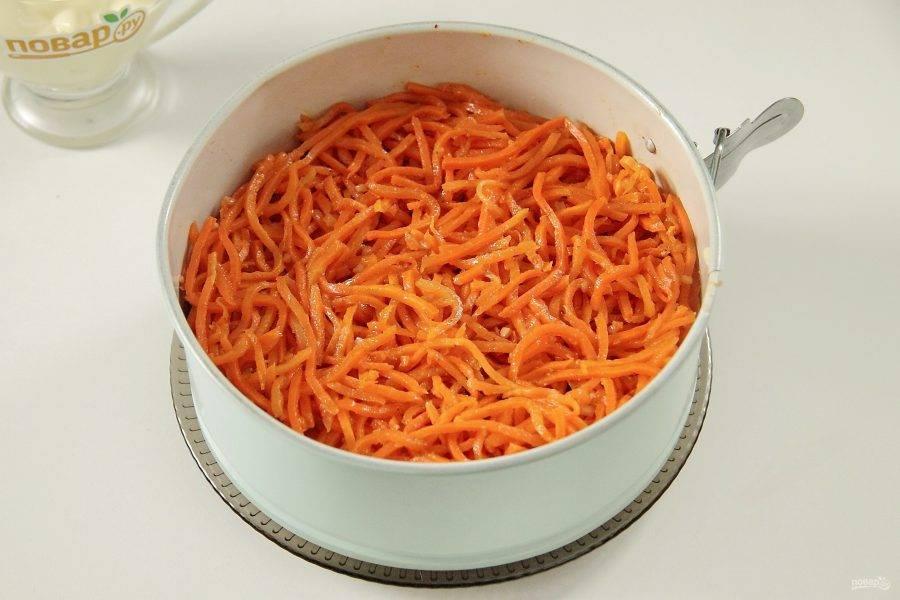 Сверху на зелень кладем морковь по-корейски. Если она достаточно длинная, то можно ее предварительно нарезать поперек на несколько частей, я не измельчала.