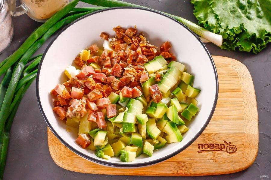 Нарежьте кубиками мясо копченой курицы: грудинку, филе, мякоть с окорочков и т.д. Удалите ядро у авокадо, счистите кожуру и нарежьте мякоть кубиками. Добавьте в емкость вместе с нарезкой курицы.