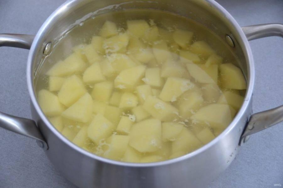 Очищенный картофель нарежьте крупным кубиком. Залейте водой примерно на 1-2 пальца выше уровня картошки, в зависимости от того, жидкое или густое блюдо вы хотите получить в готовом виде.