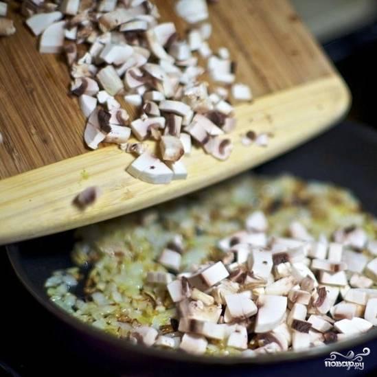 Затем добавляем в сковороду мелко нарезанные шампиньоны, перемешиваем и обжариваем еще несколько минут, помешивая, до готовности шампиньонов.