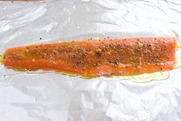 1.Вымойте филе лосося и натрите его кожуру 2 столовыми ложками оливкового масла, выложите кожей на лист фольги. Натрите на терке 3 зубчика чеснока, смешайте с цедрой одного лимона, молотым кориандром, солью и перцем, натрите полученной смесью рыбку.