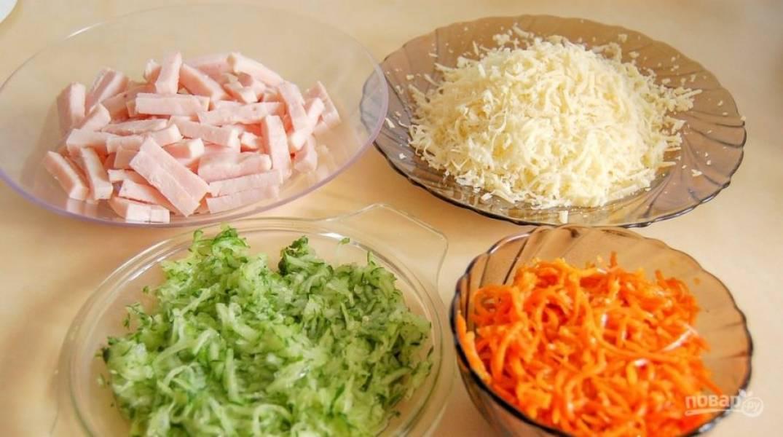 Подготовьте ингредиенты. Натрите на крупной тёрке огурец и сыр. Ветчину нашинкуйте соломкой. Яйцо отварите вкрутую.