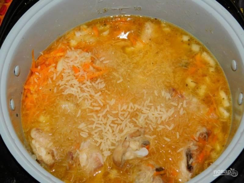 """Добавьте промытый рис и залейте водой. Установите режим """"Тушение"""" и готовьте блюдо 1 час. В процессе можно все пару раз перемешать, чтобы блюдо приготовилось равномерно."""