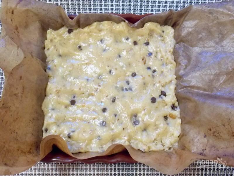 Застелите форму бумагой или ковриком для выпечки, переложите тесто и разровняйте верх.
