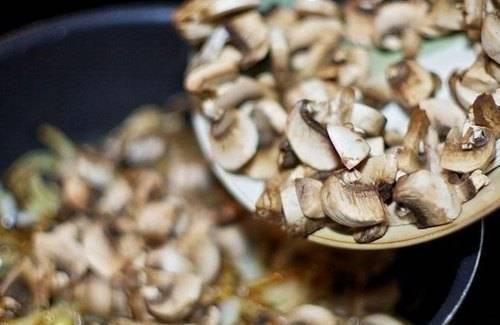 Добавьте порезанные тонкими ломтиками грибы. Жарьте до полного испарения жидкости.