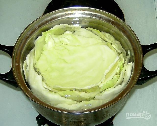 Капусту промойте, разделите на листья, опустите в кипящую воду и посолите.  Варите минут 10.