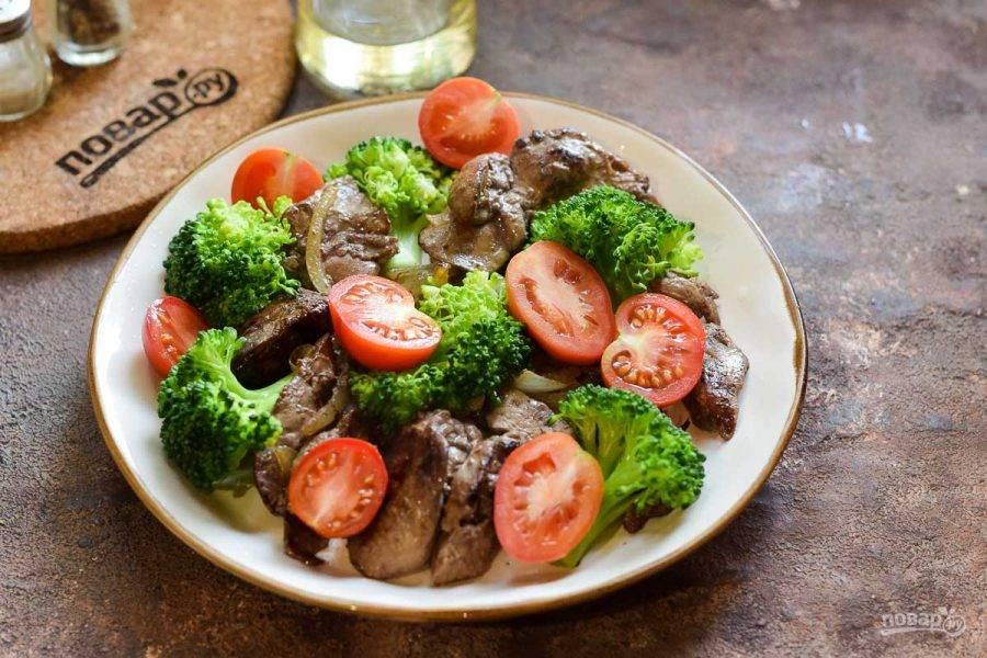 Переложите печень с луком и брокколи в тарелку, добавьте помидоры, нарезанные дольками или пополам.
