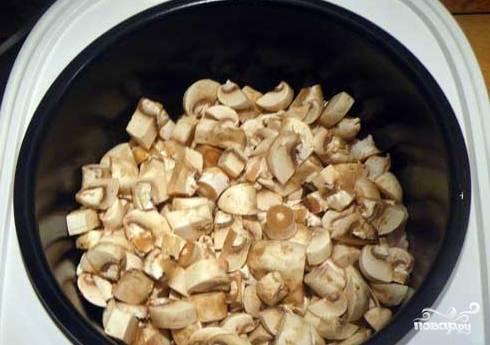 На мясо выложите слой лука и грибов.