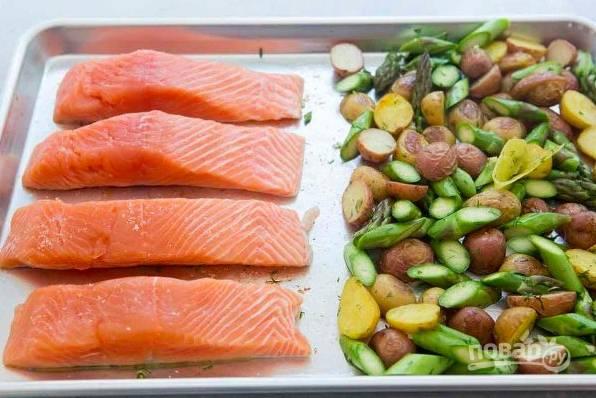 Переместите овощи на часть противня, на другую выложите чуть присоленную рыбу кожей вниз. Запекайте блюдо еще 10-12 минут, подавайте горячим.