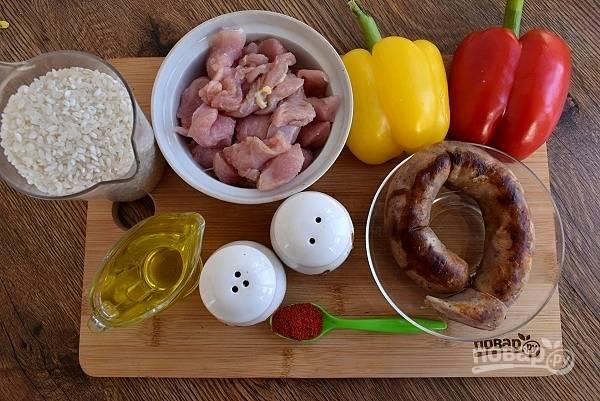 Подготовьте необходимые продукты. Духовку включите на 190 °C. Мясо нарежьте мелкими кубиками. Рис промойте в нескольких водах до прозрачной, откиньте на сито.