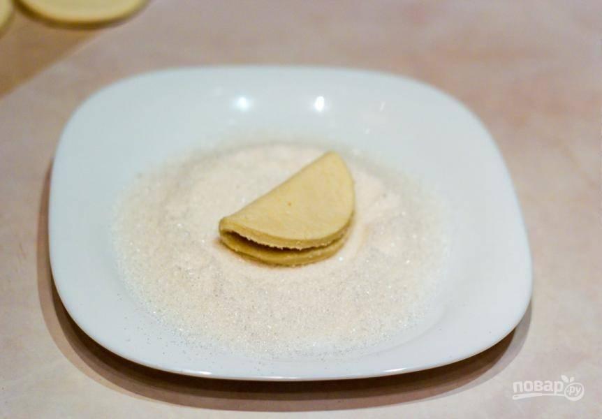 Сложите круг пополам, сахарной стороной внутрь. Тесто немного придавите.