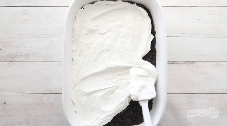 6. Половиной крема смажьте основу и отправьте десерт в холодильник на 15 минут.
