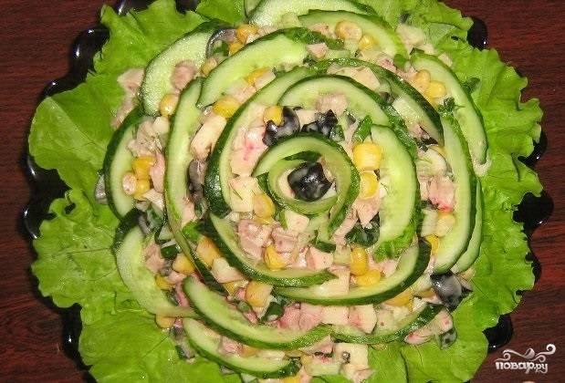 3.Моем листья салата, высушиваем и укладываем на тарелку, выкладываем заправленный салат. Второй огурец моем и нарезаем сначала продолговатыми кружочками, а потом еще перерезаем наполовину и украшаем салат сверху. Перед подачей настаиваем 15-30 минут, приятного аппетита!