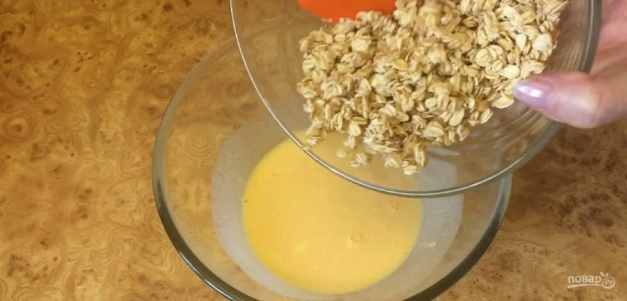 1. Геркулес залейте водой и дайте настояться в течение 20-30 минут. Желтки смешайте со сметаной и добавьте настоявшийся геркулес. Добавьте просеянную овсяную муку и вымесите тесто лопаткой.