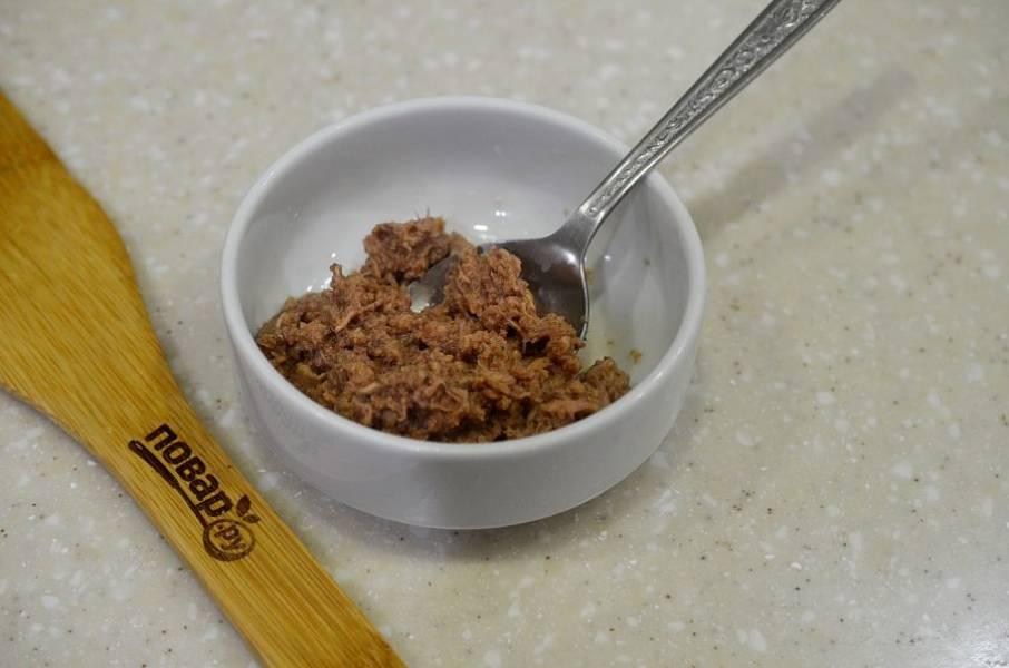 5. Тунца разомните вилкой и выложите следующим слоем. Смажьте небольшим количеством заправки.