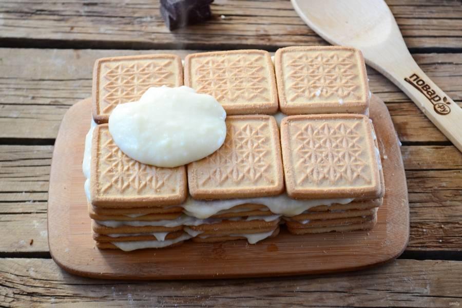 Снова накройте печеньем и смажьте кремом. Так продолжайте со всем остальным печеньем. Готовый торт сверху и по бокам смажьте остатками крема. Сверху присыпьте тертым шоколадом.