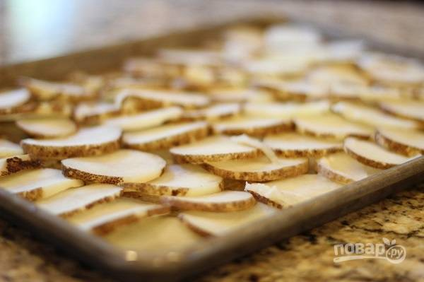 3. Выложите картофель на противень. Посолите и поперчите его по вкусу.