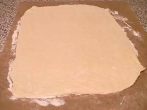 Возьмите готовое тесто, раскатайте его на присыпанной мукой поверхности довольно тонко, удобно это делать прямо на пекарской бумаге (потом прямо на ней можно будет перенести тесто на противень). В итоге у вас должен получиться своего рода прямоугольник размером примерно 40 см. на 25 см.