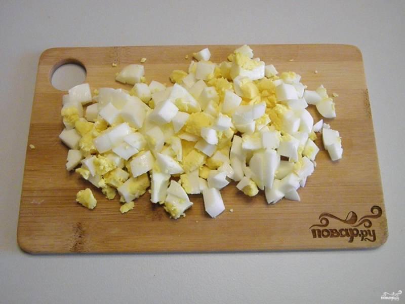 Отваренные вкрутую яйца нужно очистить от скорлупы. Порежьте их кубиками, как и филе.