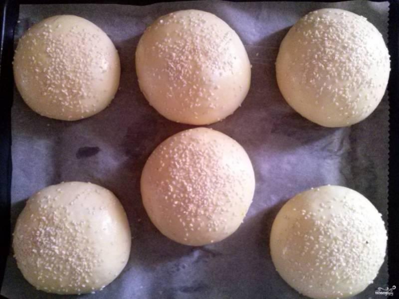 Разогрейте духовку до 200 градусов. Размешайте в миске 1 яйцо с 1 ч.л. воды, смажьте подошедшие булочки. Посыпьте сверху кунжутом.