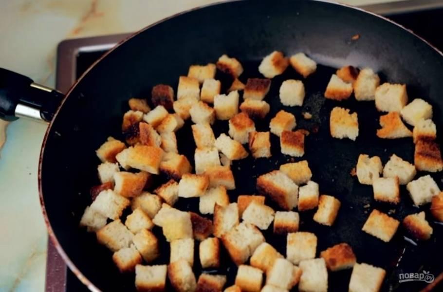 1. Для начала приготовьте сухарики. Для этого хлеб или булку нарежьте на небольшие кубики и подсушите вместе с мелко нарезанным чесноком на сковороде, смазанной оливковым маслом, до золотистого цвета.