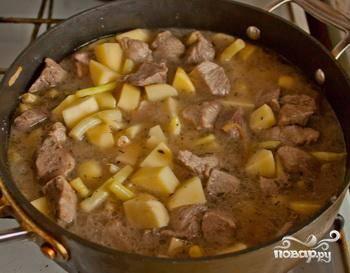 Пожарив картофель около 5 минут, возвращаем мясо обратно и все заливаем бульоном, снова солим и добавляем приправ по вкусу. Доводим на сильном огне до кипения и уменьшаем огонь, накрываем крышкой и тушим до мягкости мяса, около 40 минут. За 5 минут до готовности кладем в сотейник измельченный чеснок. Готово!