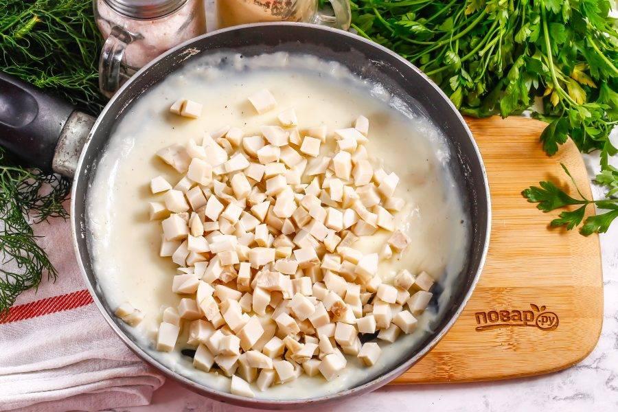 Отварные кальмары нарежьте мелкими кубиками и всыпьте в соус, перемешайте.