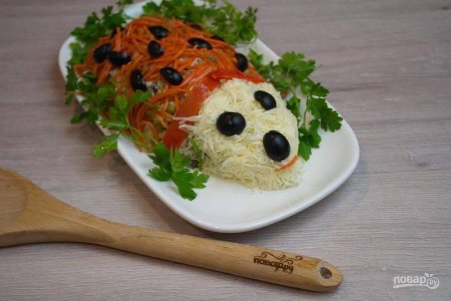7. Остальную часть тела покройте корейской морковкой, отжатой от маринада, чтоб готовый и настоявшийся салат не потек. Из оливок-маслин сделайте глазки, носик, иголочки. Украсьте края блюда зеленью и дайте салату постоять 10-15 минут в холодильнике.