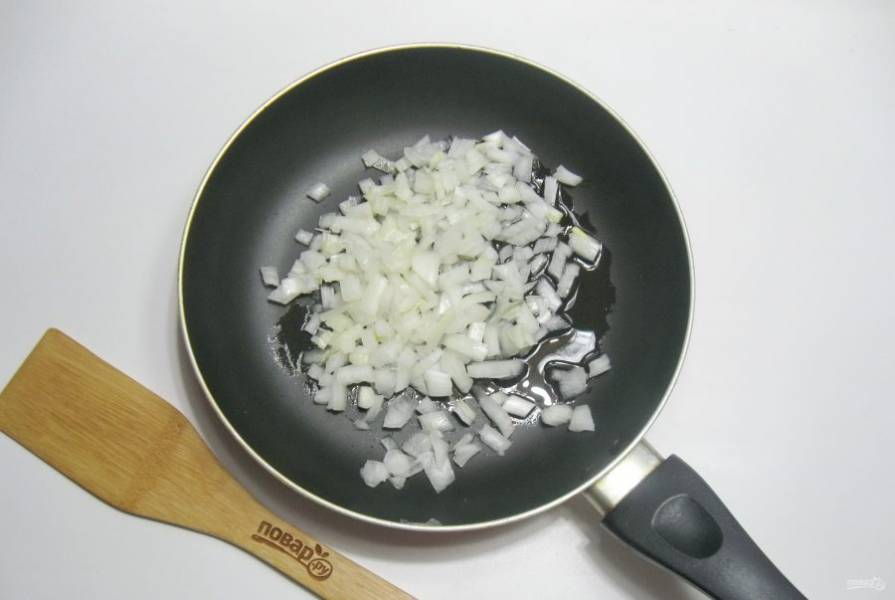 Пока тесто отдыхает, приготовьте начинку. Лук очистите, помойте, мелко нарежьте и выложите в сковороду.