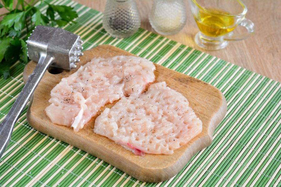 Куриное филе промойте, нарежьте пластинками и отбейте с помощью молоточка. Мясо поперчите и посолите.